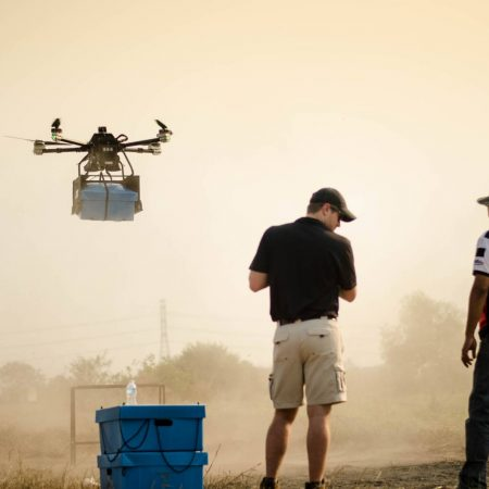Drone holding Skybox hovering during Cobra Gold military exercise with Potter operator with control and Thai military officer in foreground