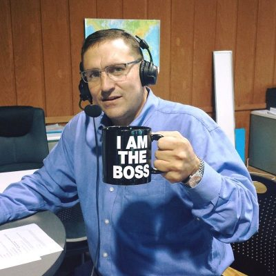 CEO Jeffrey Potter in radio studio wearing headsets with boom mic holding coffee mug which says I AM THE BOSS