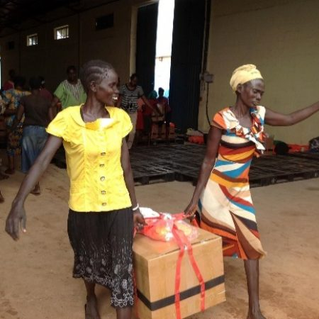female Sudanese aid workers carrying box of supplies at SkyLIFE staging facility in Africa