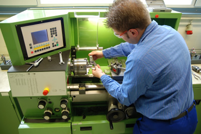 Potter engineer wearing safety glasses in industrial setting adjusting equipment with parts, hand tools and display monitor visible
