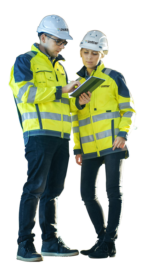 male and female Potter engineers wearing yellow safety jackets and hardhats on job site viewing tablet