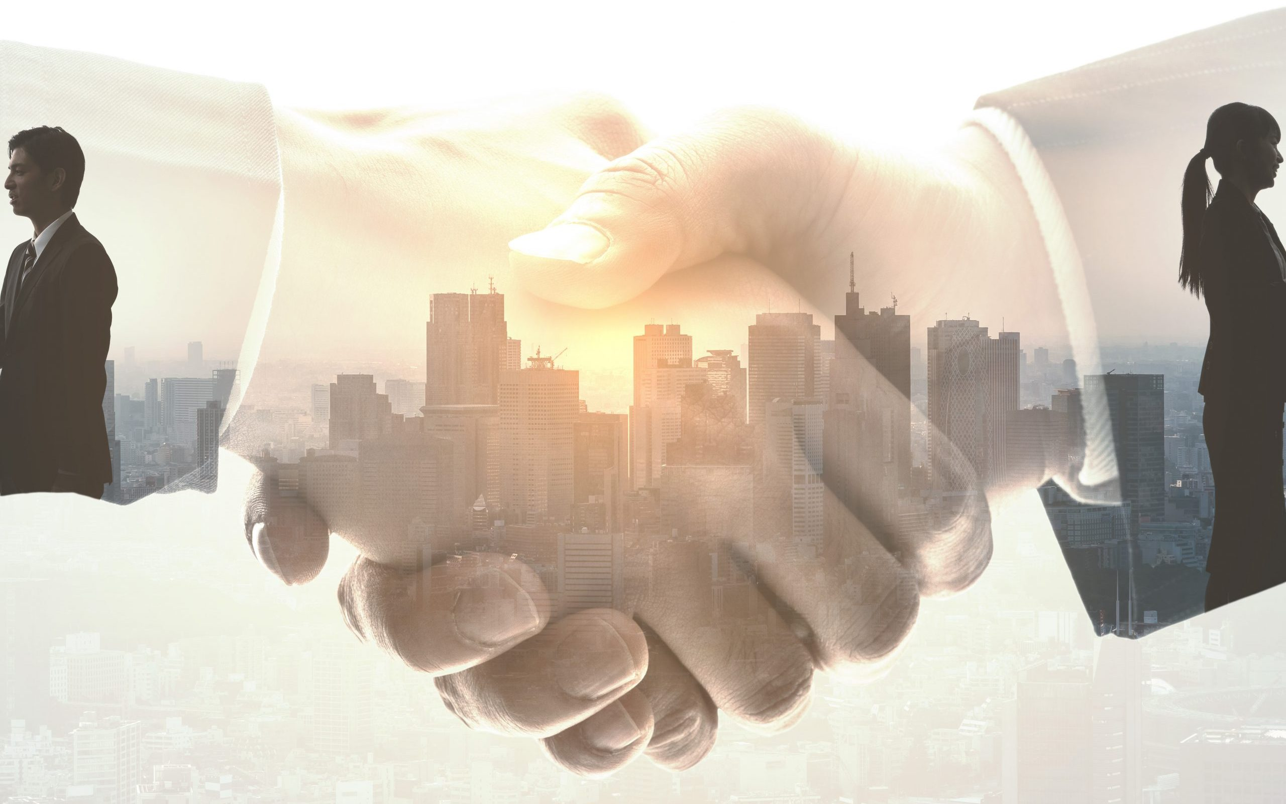 Partnership of business city skyline silhouette imposed within shaking hands