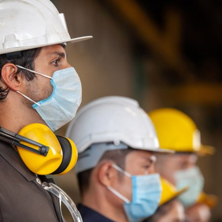 workers wear protective face masks and hard hats in industrial setting